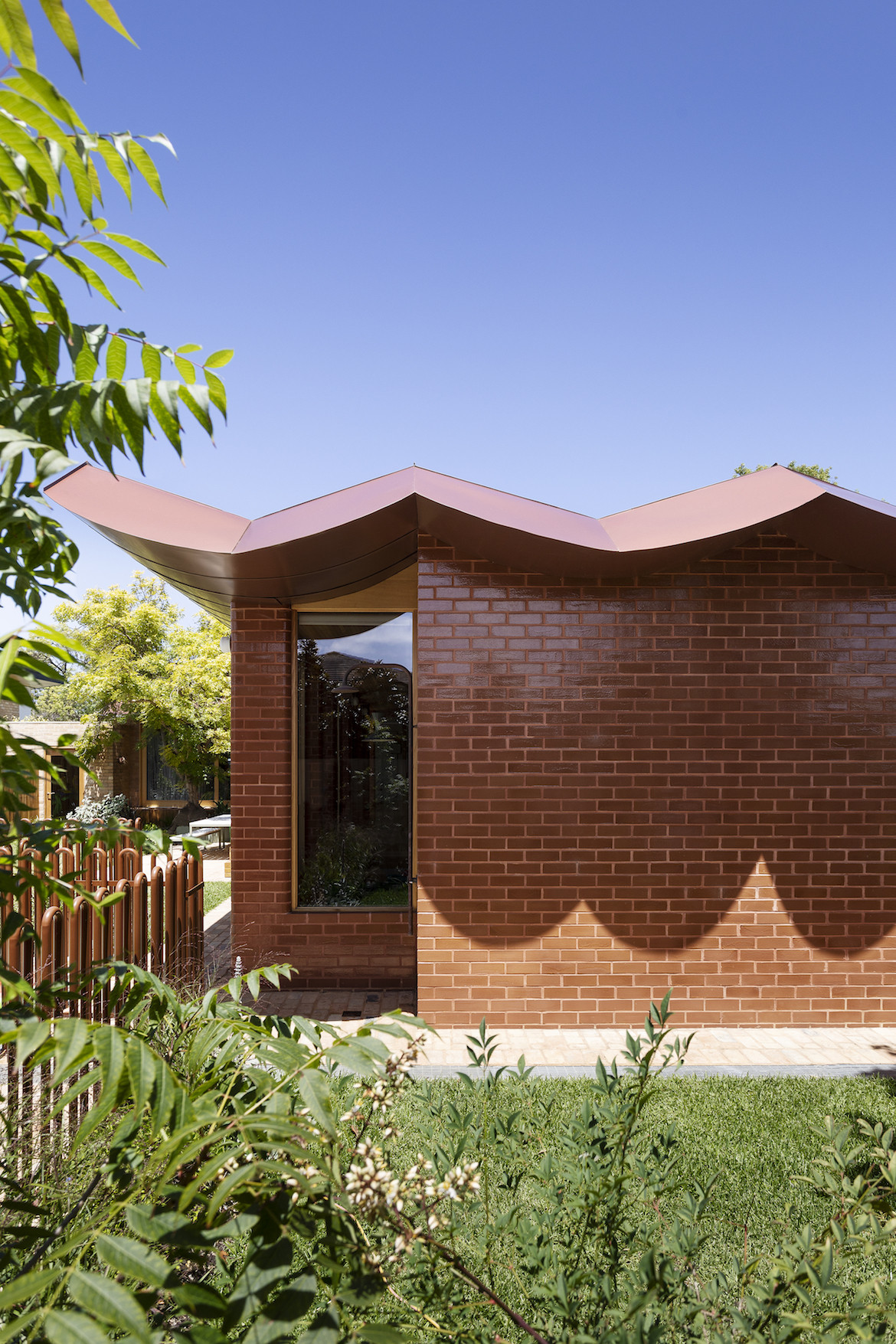 Inverted arched shadows on the glazed brick wall of the Wowowa designed home..